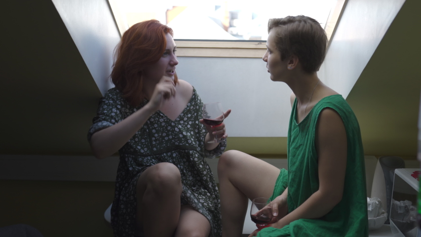 Two women chatting and drinking red wine from large glasses - Caucasian white girls laughing wearing a dotted summer dress and a green plain one | Shutterstock HD Video #1032228782