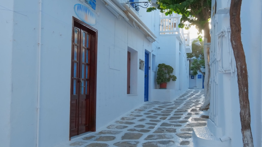 Walking with steadycam steadicam in picturesque scenic narrow streets with traditional whitewashed houses with blue doors windows of Mykonos town in famous tourist attraction Mykonos island, Greece