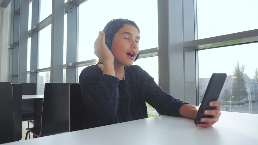 Happy young teenage girl in headphones sings and listening to the music on smartphone. teenager girl in social networks listens to music sitting in a lifestyle cafe | Shutterstock HD Video #1032243224