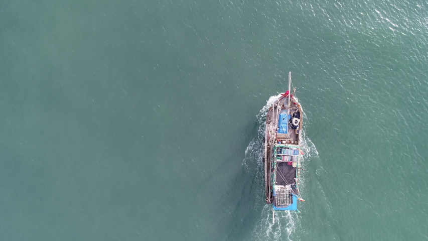 Top view, aerial view fishing boat on the beach from a drone. High-quality free stock of view from above of the wooden fishing ship offshore moving to harvest seafood on the beach, ocean surface