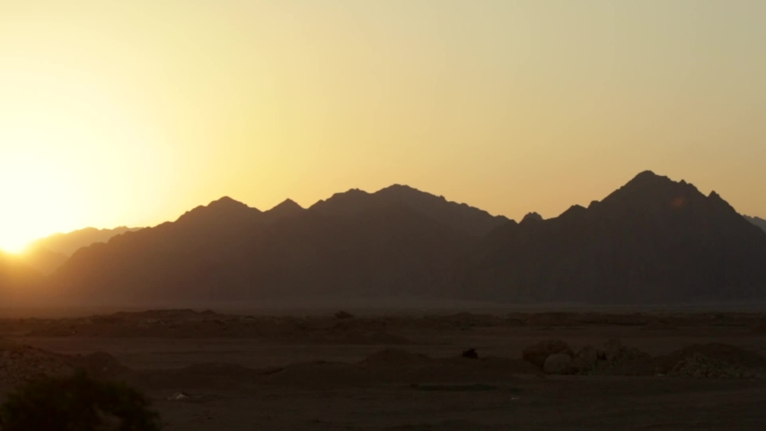 The road in the desert, the view of the mountains from the window of a moving car. Sunset in the desert. Fast motion. Road trip. Egypt