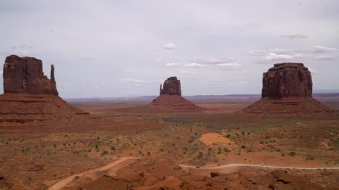 Time-Lapse: Cloudsing over monument valley during the day, cars driving on the dirt road in front
