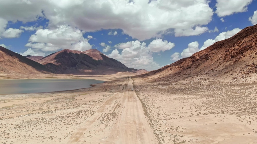 Aerial over off road 4x4 car driving along gravel trail path near arid desert mountains.Pamir Highway silk road trip adventure in Kyrgyzstan and Tajikistan desert,central Asia.4k drone flight video