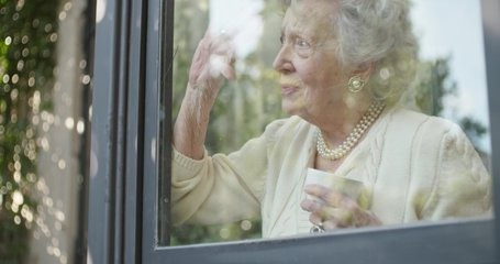 Senior grandma woman drinking cup of tea or coffee near window looking outside worried or sad or thinking.Beautiful white hair elderly grandmother at home.View from outside.4k slow motion video