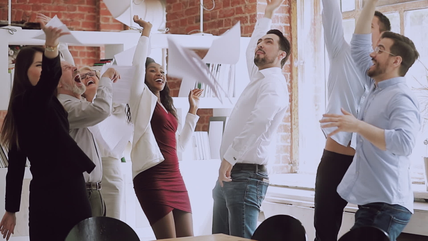 Happy funny diverse business team people dancing tossing papers celebrate success reward at office party, corporate multiracial staff group excited by good work results enjoy victory dance concept