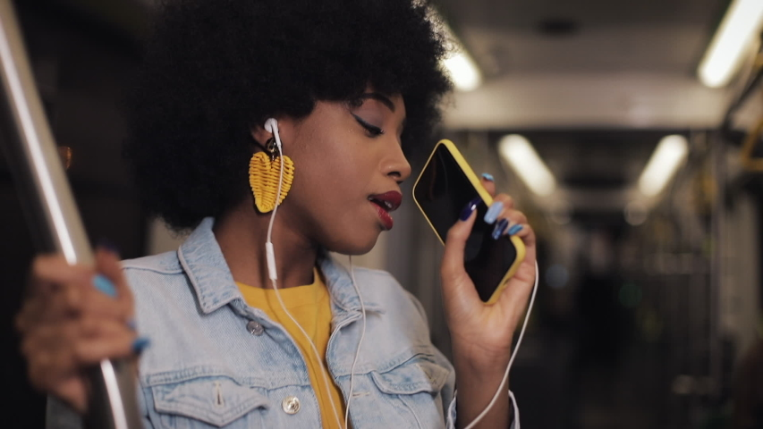 Portrait of young african american woman with headphones listening to music, sing and funny dancing in public transport. He holds the handrail.