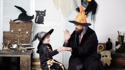 Father and son having fun at home. Happy Family preparing for Halloween. Dad and child are happy. Halloween background. Holiday with funny carnival costumes on a halloween background