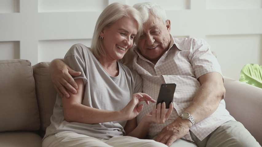 Happy old senior couple laughing using smartphone funny app looking at screen, smiling retired husband and middle aged wife talking having fun watching photos on mobile phone on sofa at home Royalty-Free Stock Footage #1032303683