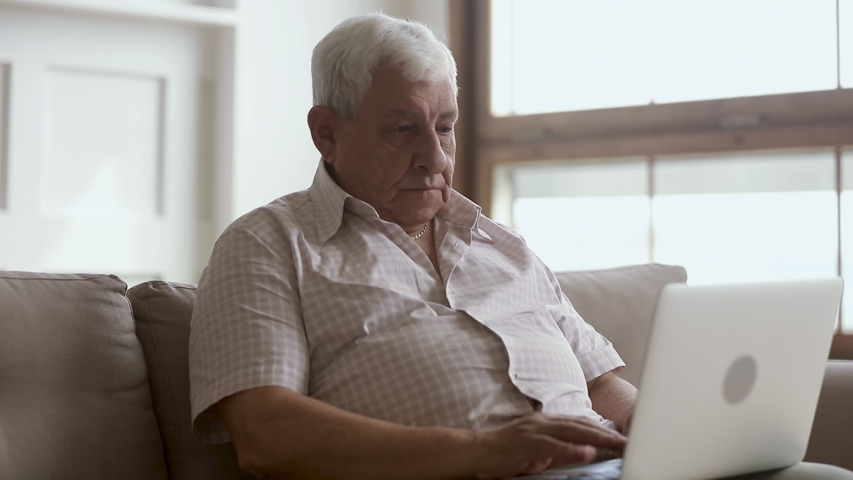 Senior older mature man typing on laptop laughing browsing internet using apps sit on sofa alone, elder aged retiree working on computer looking at screen at home, retirement and technology concept