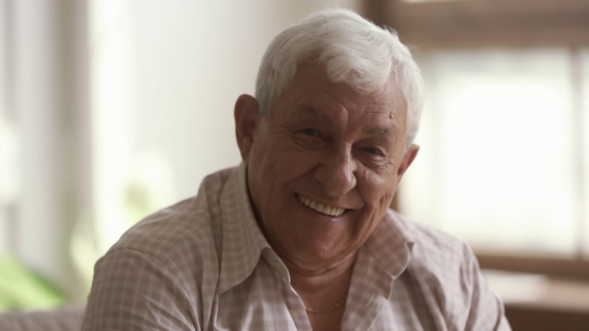 Senior old gray-haired man looking at camera, serious happy elder mature grandfather with toothy smile posing for close up video portrait alone at home or retirement house, older people health care #1032303701