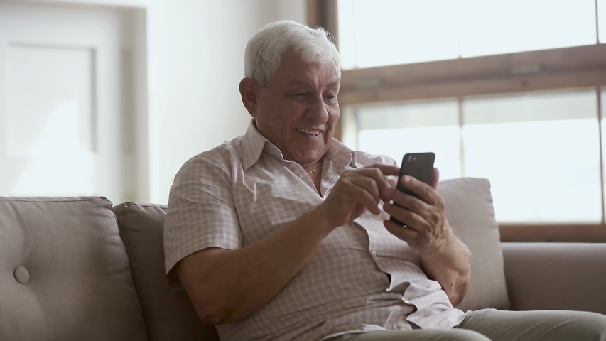 Happy elder senior man holding smartphone using mobile online app, smiling old aged grandpa texting sms message