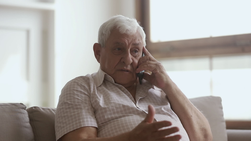 Happy elder senior man holding cellphone talking on phone at home, smiling older retired mature grandfather making call enjoy mobile telecommunication laughing speaking by smartphone sit on sofa