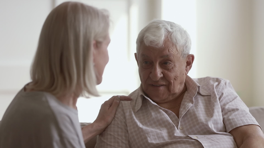 Loving understanding middle aged wife or caregiver listening to senior husband helping with problem, old couple talking at home, mature woman comforting giving support to grey haired elder man patient