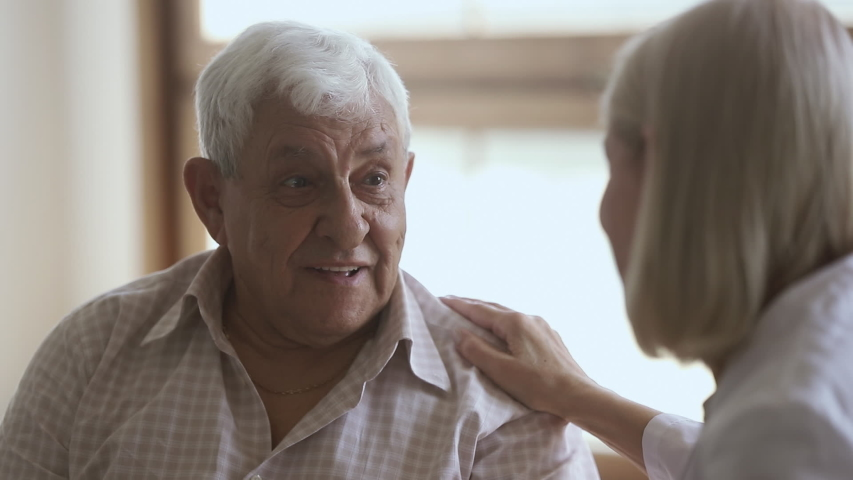 Elder old man talking to mature doctor caregiver telling complaints laughing, female nurse listening supporting senior patient having trust conversation giving care helping providing medical services