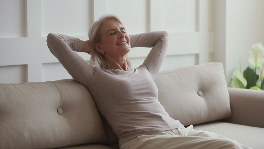 Happy lazy middle aged woman relaxing sit on couch at home, smiling calm mature old lady chilling hands behind head lounge on sofa enjoy comfort no stress free weekend peaceful rest dreaming at home | Shutterstock HD Video #1032303740