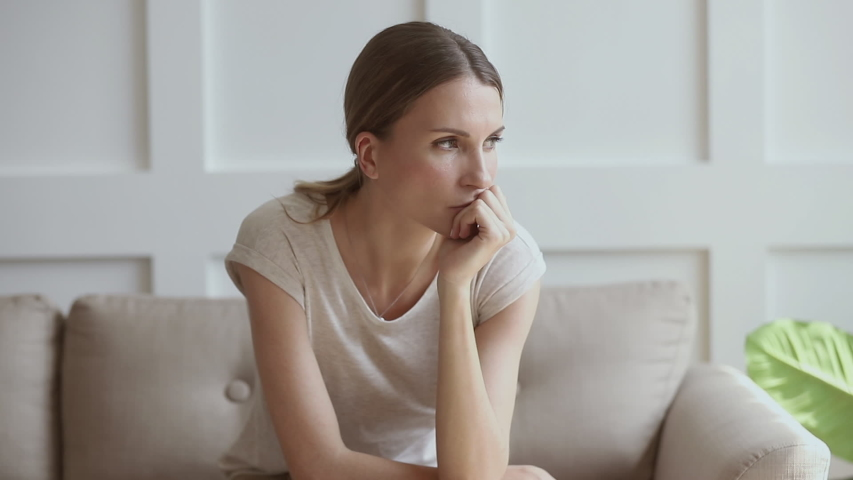 Worried insecure young lady thinking of problem sitting alone at home thoughtful depressed woman feeling concerned doubtful making difficult decision troubled with anxiety, doubt or unwanted pregnancy   Shutterstock HD Video #1032303761