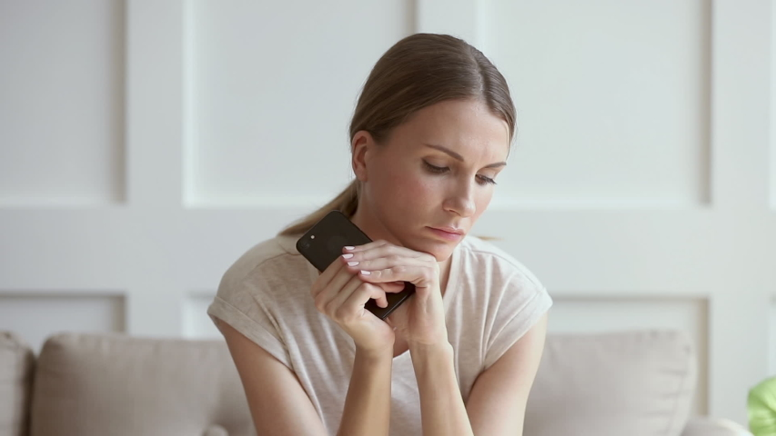 Jealous worried young woman holding phone feeling jealousy anxiety waiting for mobile call sit alone  at home, thoughtful stressed doubtful lady looking at smartphone thinking of cheating boyfriend