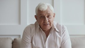 Happy senior elder man looking talking to camera recording vlog or making call at home, old grey-haired aged grandfather doing video chat or shooting footage for channel, webcam view