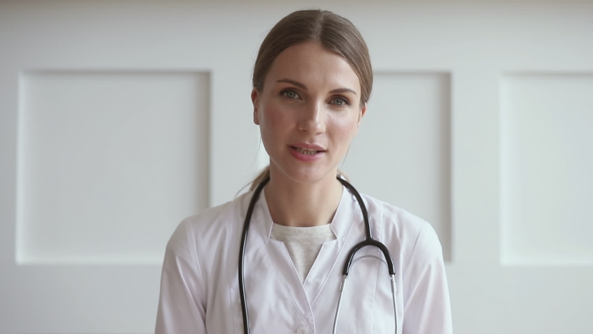 Young professional woman doctor wear uniform with stethoscope talk by conference video call chat consult patient online looking at camera webcam, distant medical consultation in internet app concept