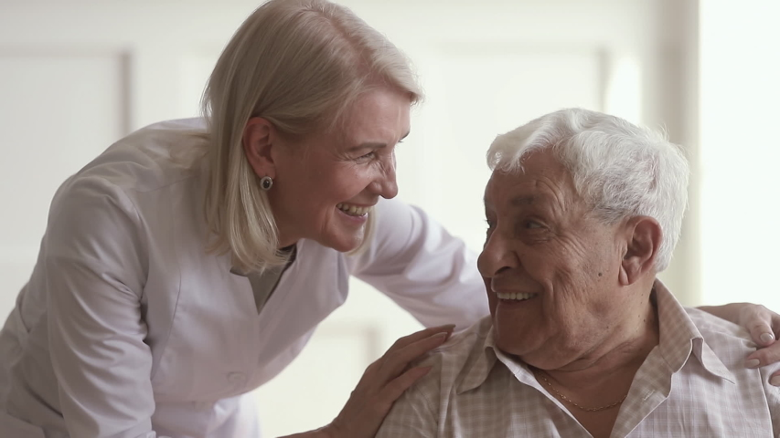 Smiling mature kind woman nurse doctor talking to happy disabled old elder man, happy female therapist cheering taking care of senior patient giving support and medical assistance in retirement house