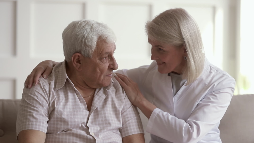 Kind mature woman nurse caregiver supporting talking to old elder man help with problem, female doctor therapist in uniform on sofa at home hospital cheering give empathy listen to senior patient