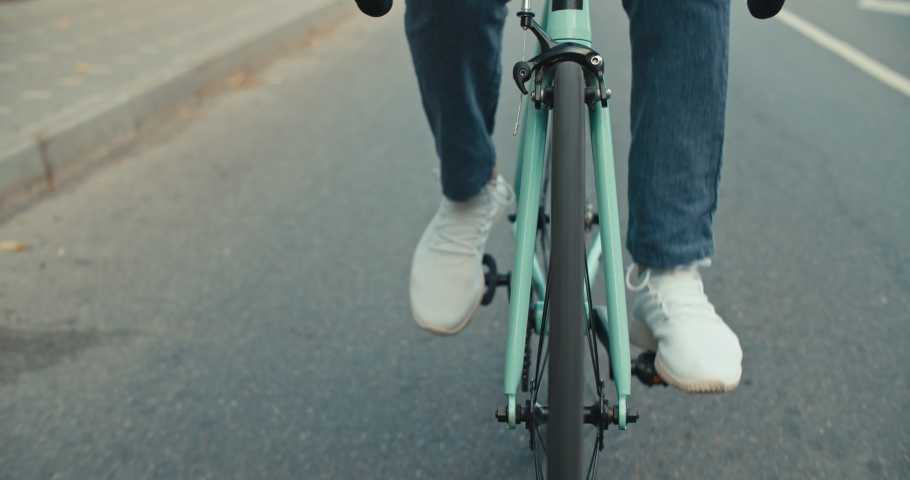 Cyclist guy riding fixed gear sport bike in sunny day on city. Hipster man in casual summer cloths and bicycle on street. Front tracking close-up of wheels. 4K slow motion raw video footage 60 fps   Shutterstock HD Video #1032305906