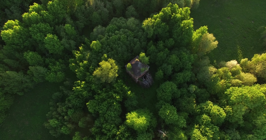 4K high quality early summer sunny afternoon aerial video footage of abandoned village site with ruins of old vintage church in the middle of dense green wild woods in Russia's Yaroslavl region | Shutterstock HD Video #1032314561