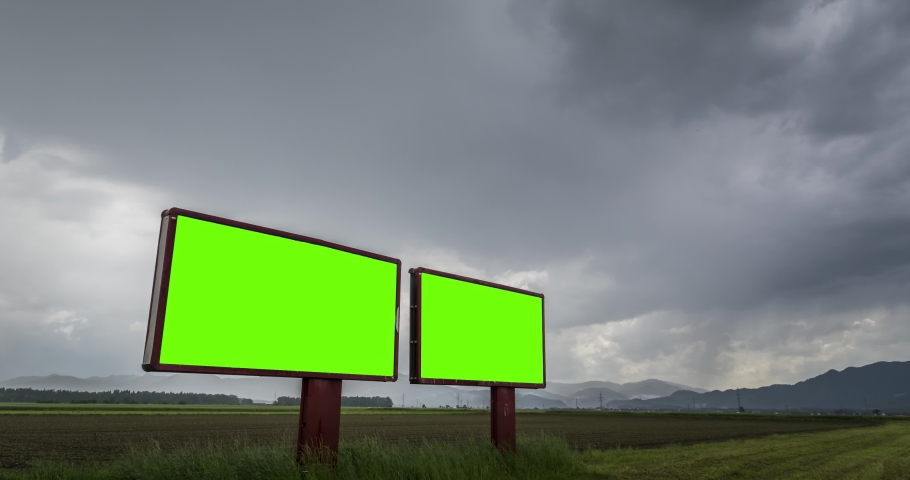 Green screen billboards timelapse in a countryside with a farming field area behind it and hills in the background on a stormy day. | Shutterstock HD Video #1032321722