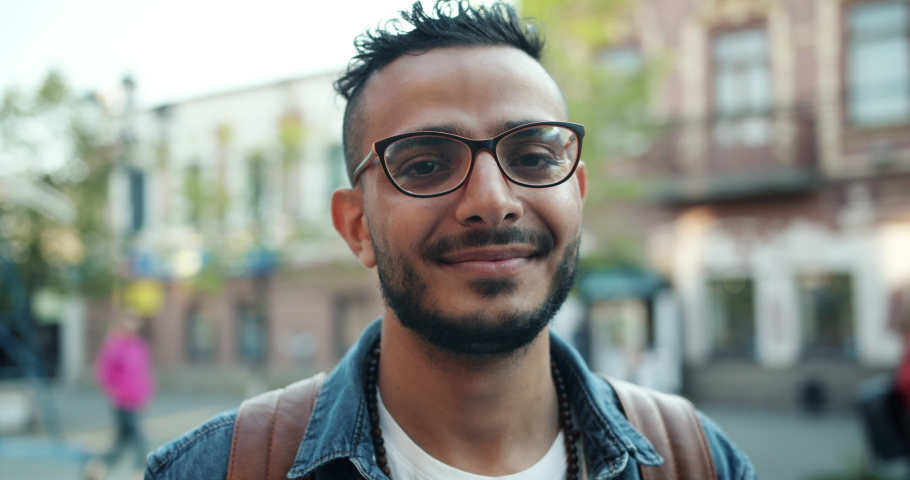 Close-up portrait of young handsome Arab standing outdoors alone smiling looking at camera. Beautiful people, city lifestyle and urban youth concept. | Shutterstock HD Video #1032331340