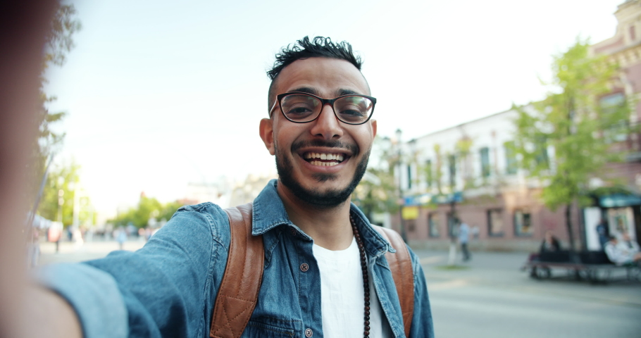 POV slow motion shot of young bearded Arab making online video call talking looking at camera outdoors holding gadget with camera standing in the street. | Shutterstock HD Video #1032331397