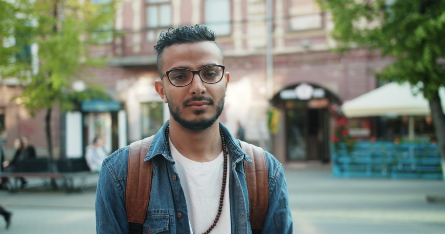 Slow motion portrait of attractive Arabian man in stylish clothing standing outdoors with serious face then smiling looking at camera. People and emotions concept. | Shutterstock HD Video #1032331430
