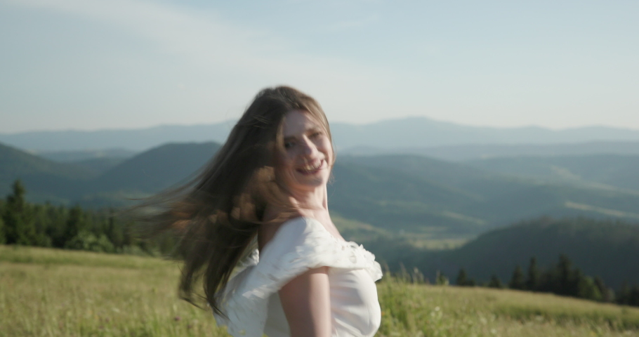 Attractive woman run on a mountain peak with her long hair blowing in the wind smiling and trying to keep her hair off her face   Shutterstock HD Video #1032331676
