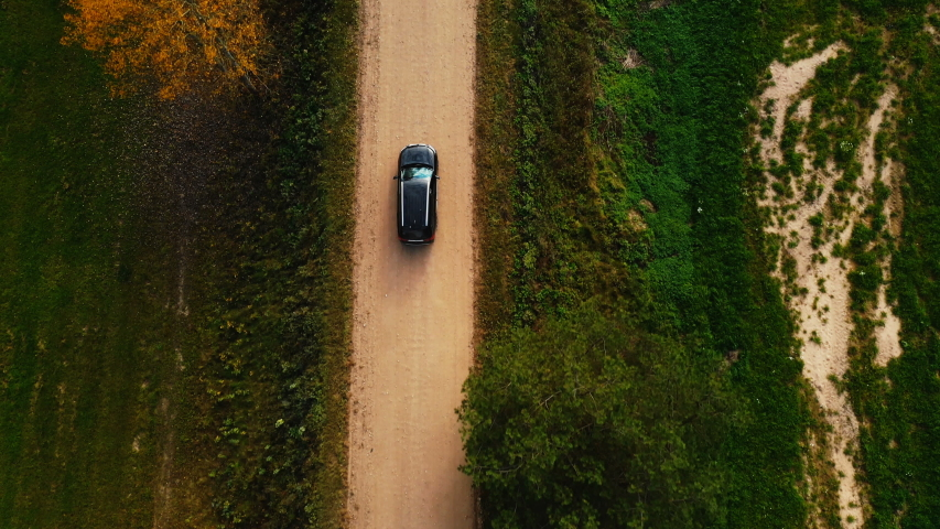 Top view aerial tracking shot of black car moving on gravel road along yellow autumn trees and countryside fields.