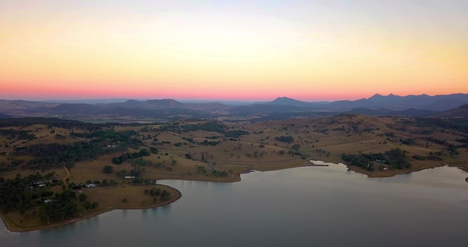 Rising aerial view of brown hills and mountains surrounding lake Moogera at sunset - Queensland, Australia. Golden, pink horizon. | Shutterstock HD Video #1032357047