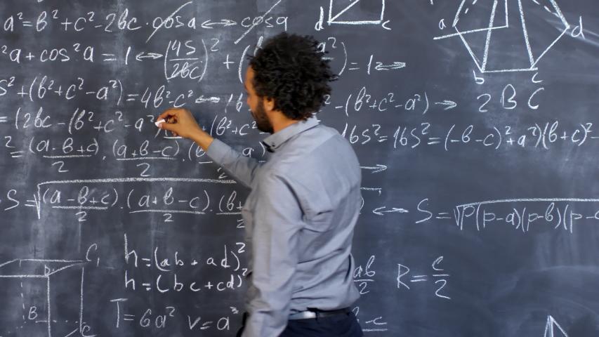 Rear view of male university professor solving complex calculus problem on blackboard | Shutterstock HD Video #1032365996
