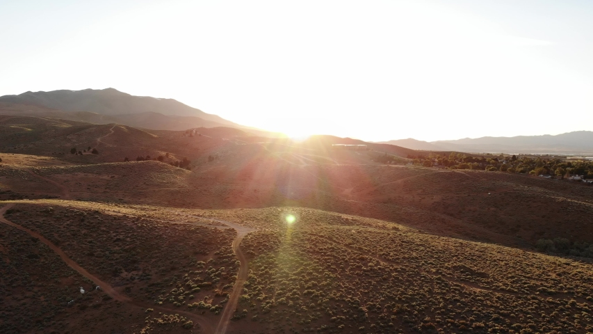Dirt Bike Rides into Flared Sunset Leaving Dust Trail - Wide Aerial Drone. | Shutterstock HD Video #1032367913