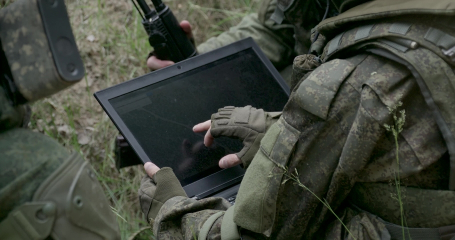 Soldiers in camouflage in ambush, military engineer uses a laptop navigation system, military action in the steppe area.