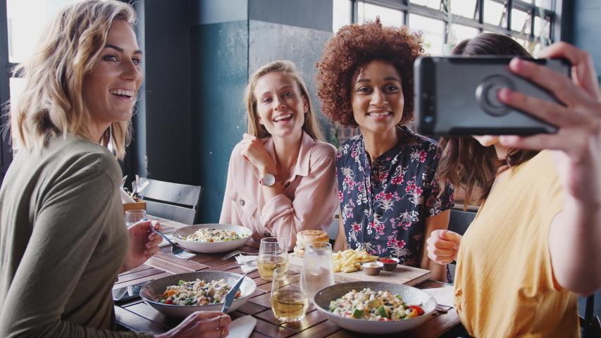 Four Female Friends Posing For Selfie In Restaurant Before Eating Meal