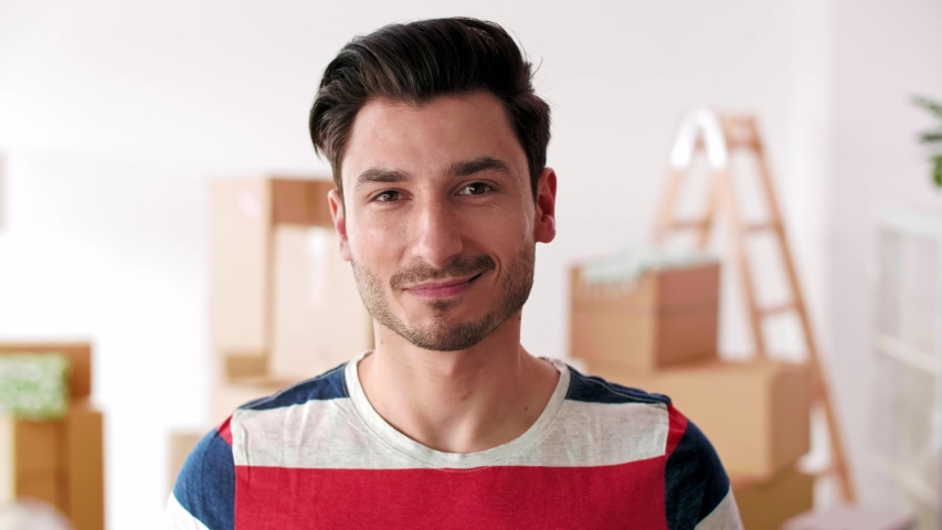 Portrait of smiling man in his new flat   | Shutterstock HD Video #1032387335