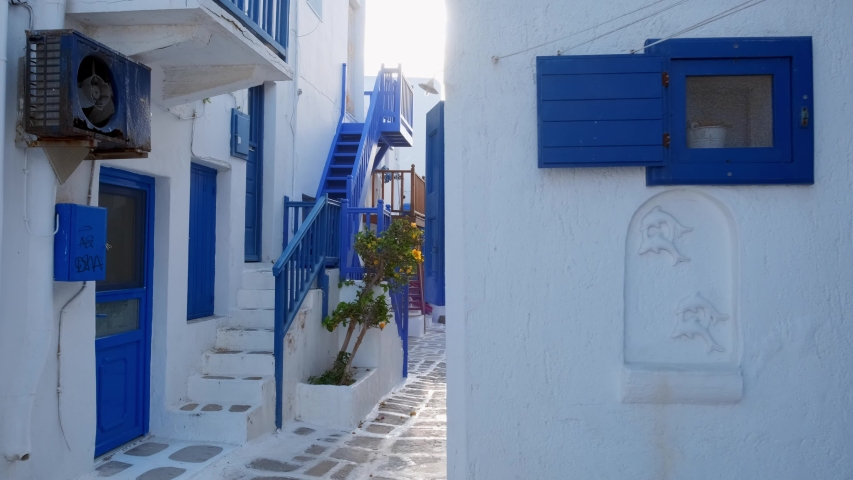 Walking with steadycam steadicam in picturesque scenic narrow streets with traditional whitewashed houses with blue doors windows of Mykonos town in famous tourist attraction Mykonos island, Greece   Shutterstock HD Video #1032388958