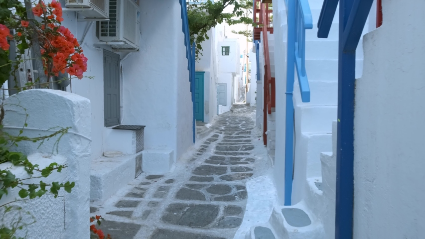 Walking with steadycam steadicam in picturesque scenic narrow streets with traditional whitewashed houses with blue doors windows of Mykonos town in famous tourist attraction Mykonos island, Greece   Shutterstock HD Video #1032388961