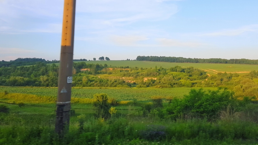 The view from the high-speed train on the beautiful scenery with hills and forest before sunset. The view from the window of the car, bus, train. Journey from the train on a sunny day