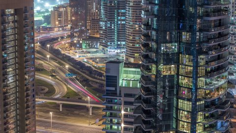 Aerial view of a road intersection in a big city night timelapse. Urban landscape of Dubai Marina and district in UAE with cars and metro