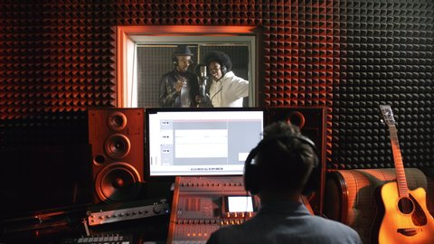Dolly-in shot of black man and woman dancing and singing into microphone in isolation booth of recording studio as male sound engineer using mixing desk in control room