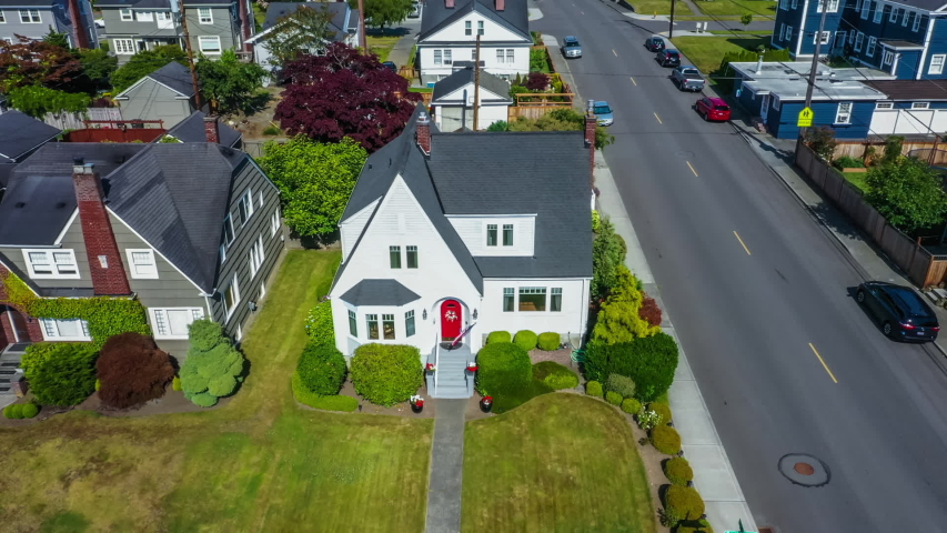 Aerial view of quaint American suburban home with realtor sign in the yard, lowering to street view.