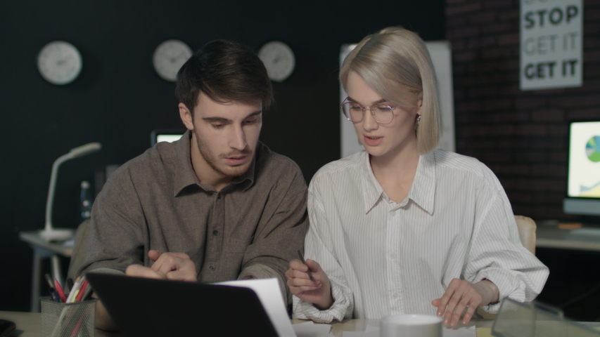 Business team analyzing business results near laptop in dark office. Business couple discussing document data in night office. Focused man and woman working overtime at workplace. | Shutterstock HD Video #1032421493