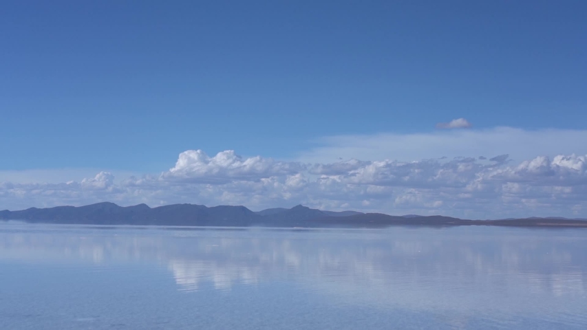 Salar de Uyuni Zoom Out establishing shot of salt flats covered in rain water, clear blue sky reflecting in clear blue water and mountains on horizon. looks like heaven in Bolivia, Latin America
