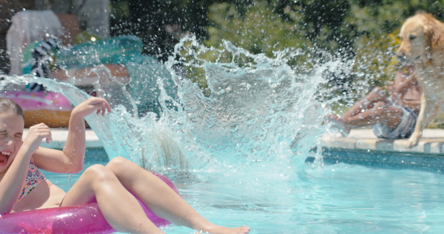 Funny little girl jumping in swimming pool splashing friend on swim tube playful dog having fun with kids enjoying summer day 4k | Shutterstock HD Video #1032443936