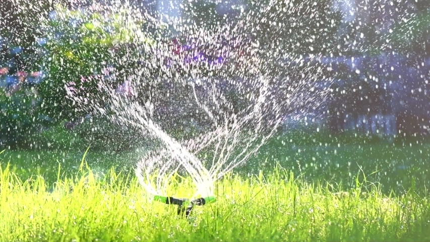 Garden Grass Watering. Smart garden activated with full automatic sprinkler irrigation system working in a green park, watering lawn, flowers and trees sprinkler head rotation. 4K UHD slow motion