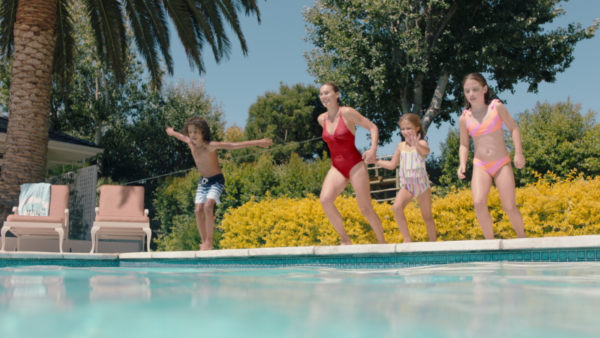 Mother with children jumping in swimming pool together happy family playfully enjoying summertime having fun splashing in cool water